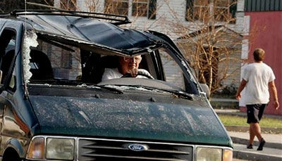 A Hurricane Katrina survivor drives his damaged van
