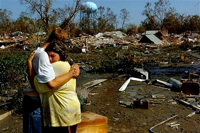 A couple embrace as they view their destroyed home