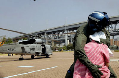 A Navy crewman comforts a distraught Hurricane Katrina survivor